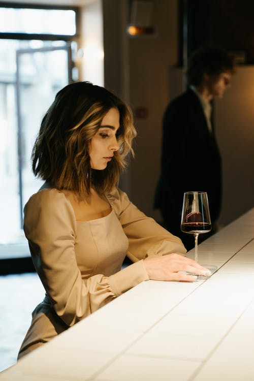 Woman in Brown Long Sleeve Shirt Sitting at the Table