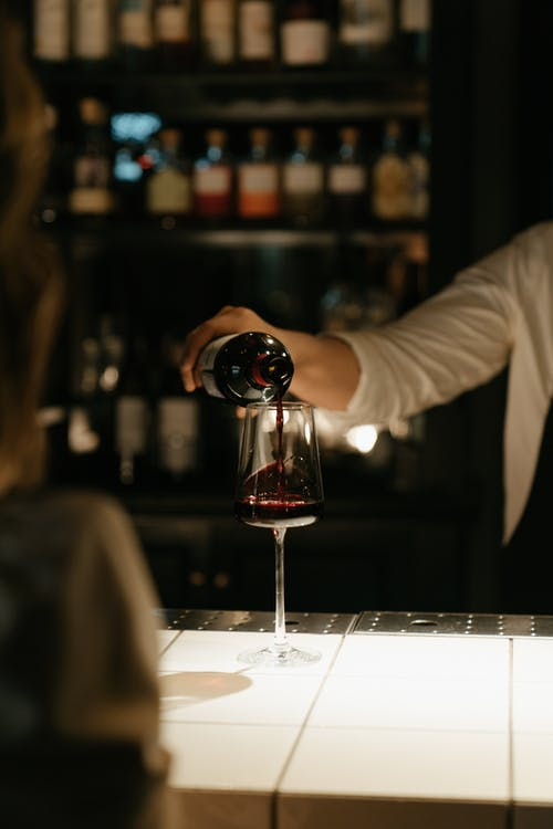Person Pouring Wine on Wine Glass