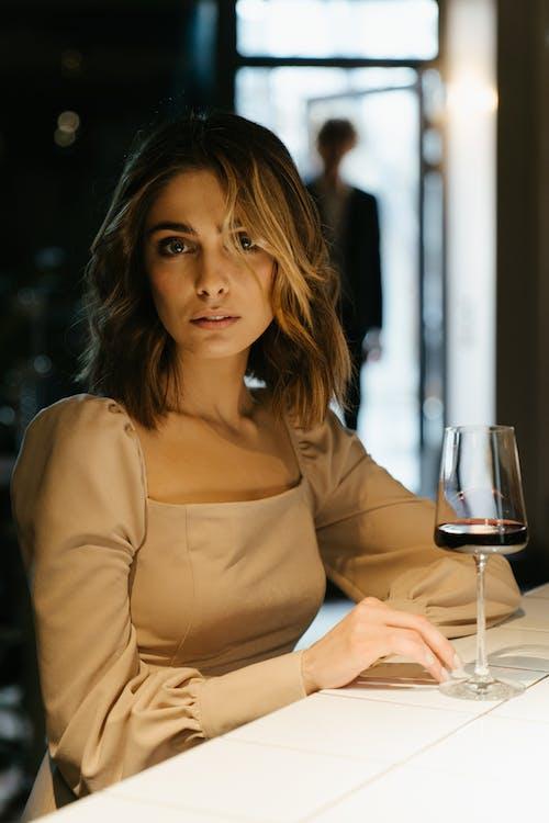 Женщина в коричневой рубашке с длинным рукавом с бокалом вина