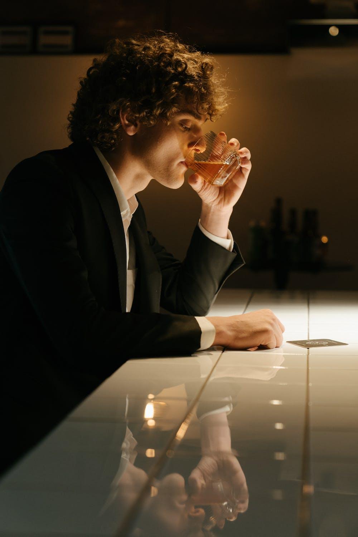 Man drinking at a bar. | Photo: Pexels