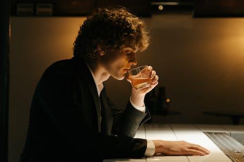Man in Black Suit Drinking Beer