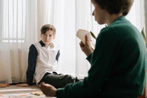 Man in Black Suit Jacket Sitting Beside Boy in White Dress Shirt