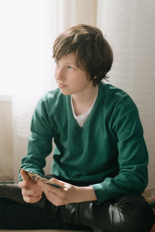 Boy in Green Sweater Holding Smartphone