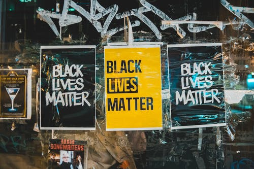 Slogan Black Lives Matter on small rectangular paper sheets on surface of painted glass