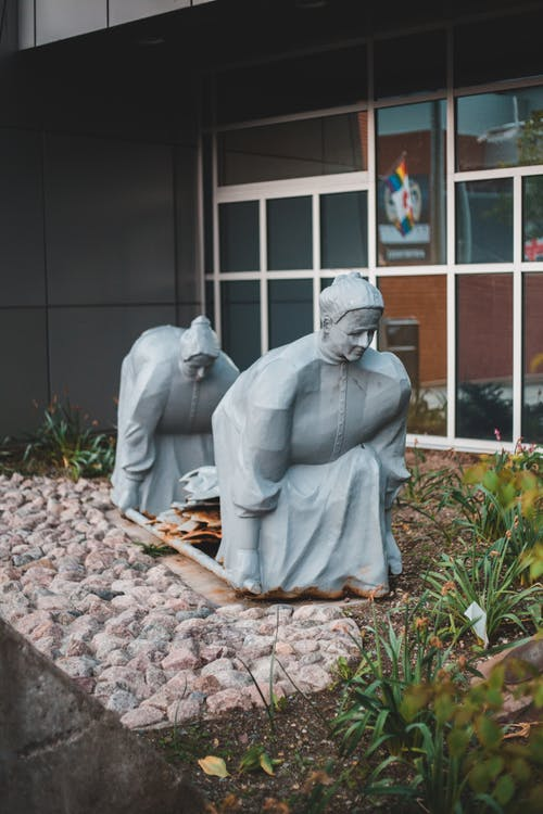 Stone gray statues of tired hunched women surrounded by decorative stones and grass near dark glass window in daylight