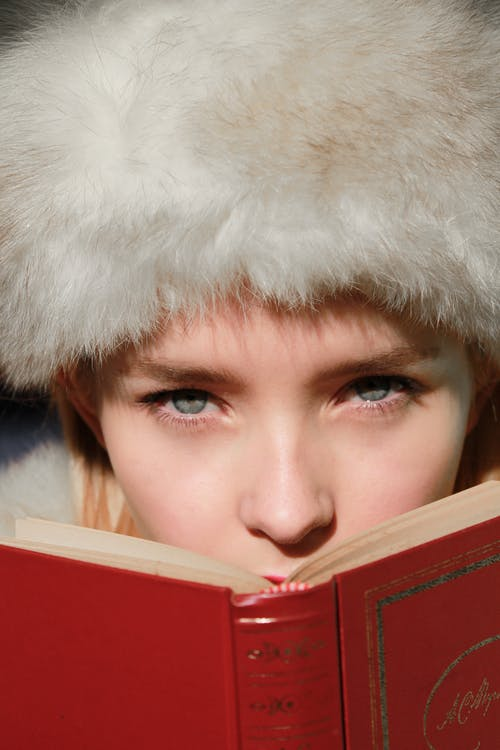 Charming young female in vintage fluffy headdress looking at camera while covering mouth with opened book in bright sunlight outside