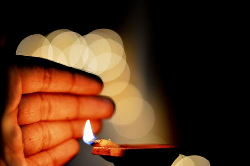 Hand Close to a Lit Diya