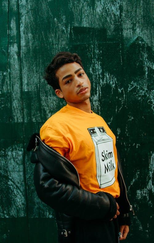 Man in Orange Crew Neck Shirt and Black Leather Jacket