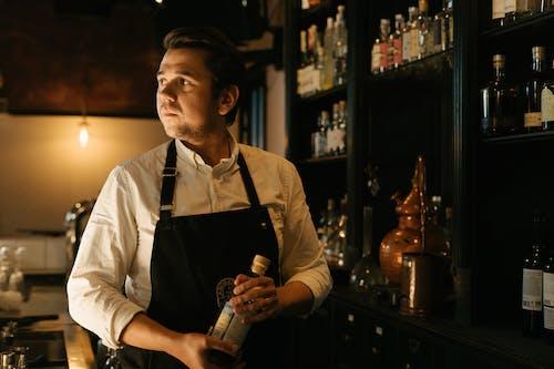 Мужчина в белой рубашке с бутылкой