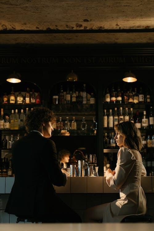 Man in Black Suit Jacket Standing Beside Woman in White Long Sleeve Shirt