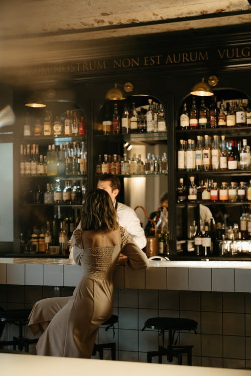 Woman in White and Black Stripe Dress Standing in Front of Bar Counter
