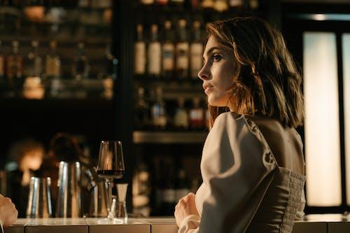 Vrouw In Witte Jas, Zittend Naast Tafel