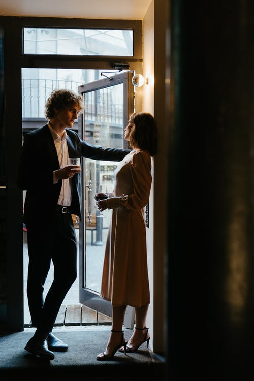 Man in Black Suit Standing Beside Woman in White Long Sleeve Shirt