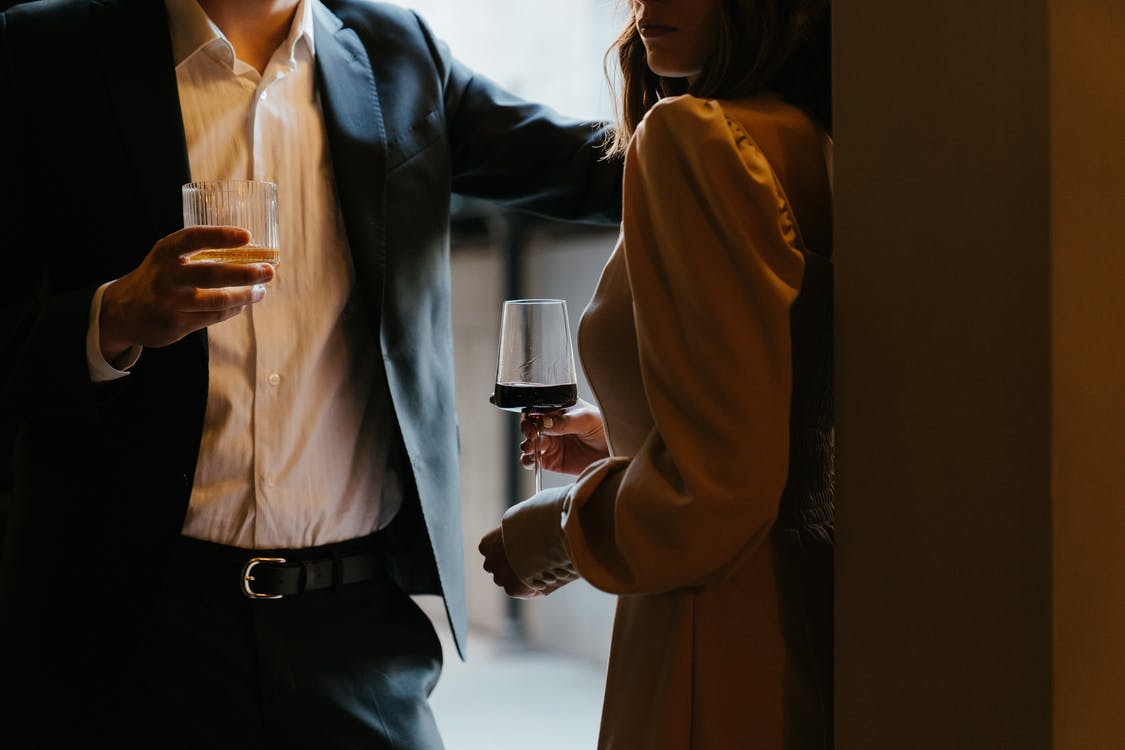Woman in White Dress Shirt and Black Blazer Holding Clear Drinking Glass