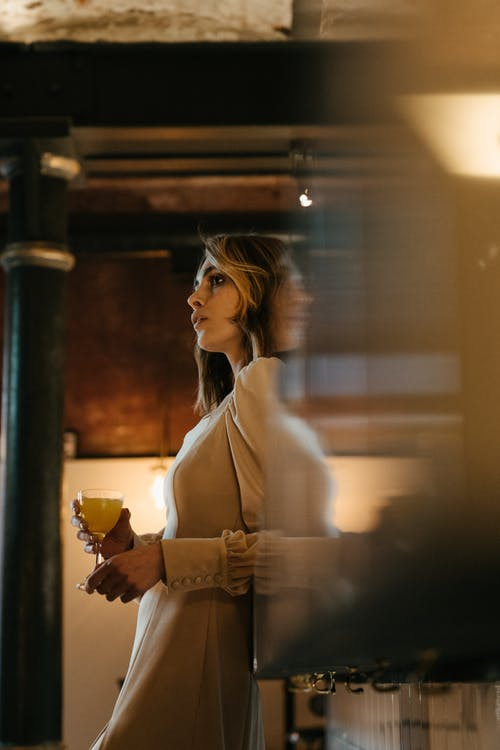 Woman in White Long Sleeve Shirt Holding Glass Cup