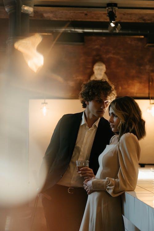黑色西裝的男人親吻棕色外套的女人