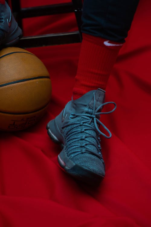 Crop anonymous sportsman in trendy runners and red socks sitting on stool with foot on basketball ball