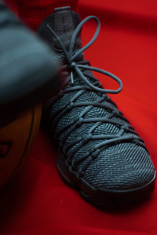 Black Lace Up Shoe on Red Background