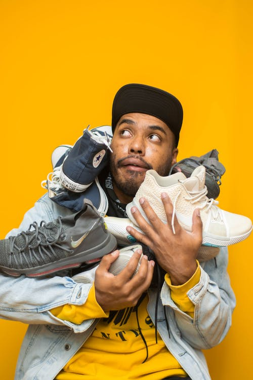 Photo of Man Looking Up While Holding Plenty of Shoes