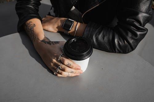 Základová fotografie zdarma na téma bez tváře, černá kožená bunda, jednorázový pohár, káva