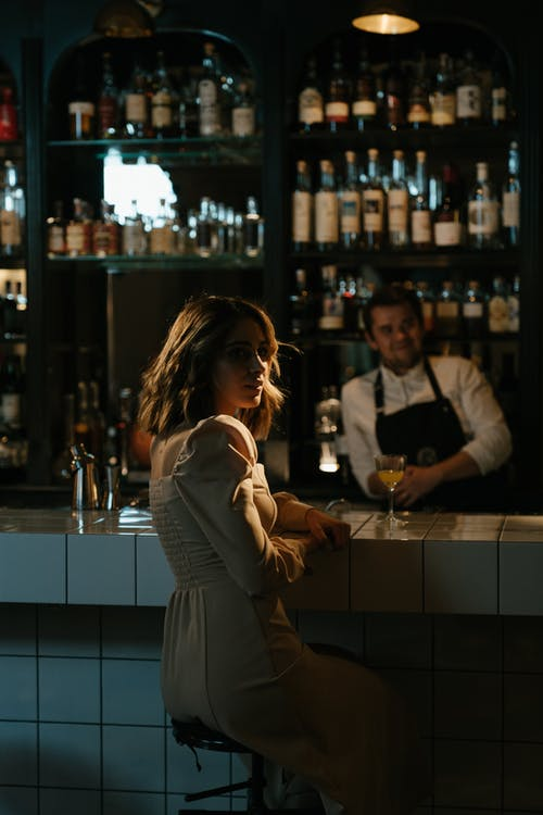 Woman in Gray Long Sleeve Dress Standing in Front of Bar Counter
