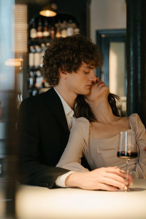 Homem De Terno Preto Beijando Mulher De Vestido Branco