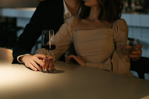 Woman in Beige Long Sleeve Shirt Holding Wine Glass