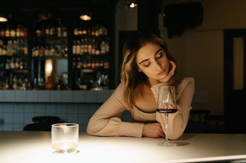 Vrouw In Bruin Shirt Met Lange Mouwen Zittend Naast Tafel Met Wijnglas