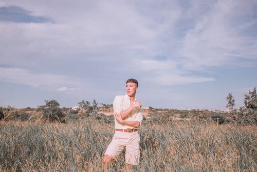 Man in White Dress Shirt and Brown Shorts Standing on Brown Grass Field Under White Clouds