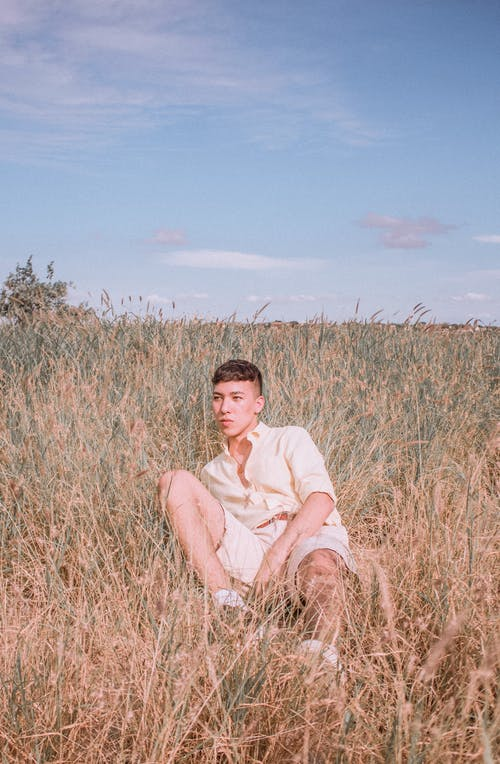 Man in Beige Dress Shirt Lying on Brown Grass Field