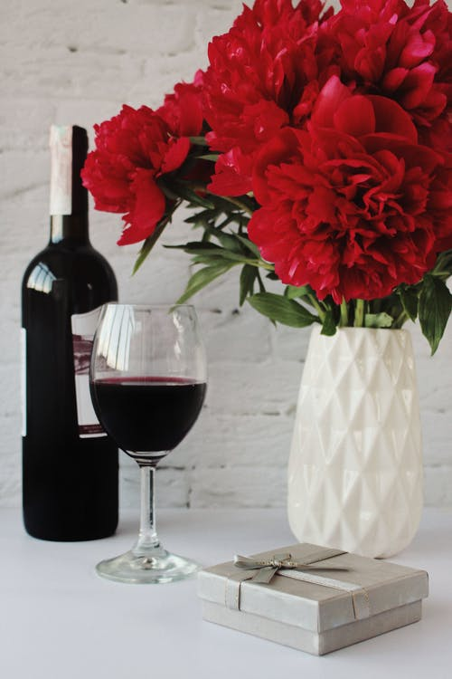 Red Rose in Clear Glass Vase Beside Wine Bottle