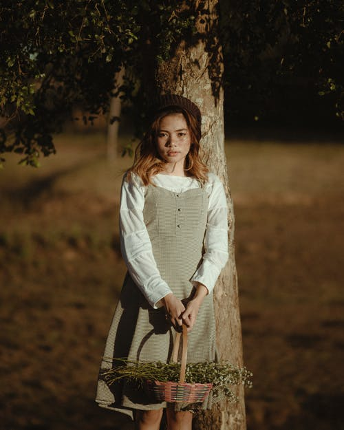 Pretty female in vintage outfit standing in park near tree holding basket full of flowers and looking at camera