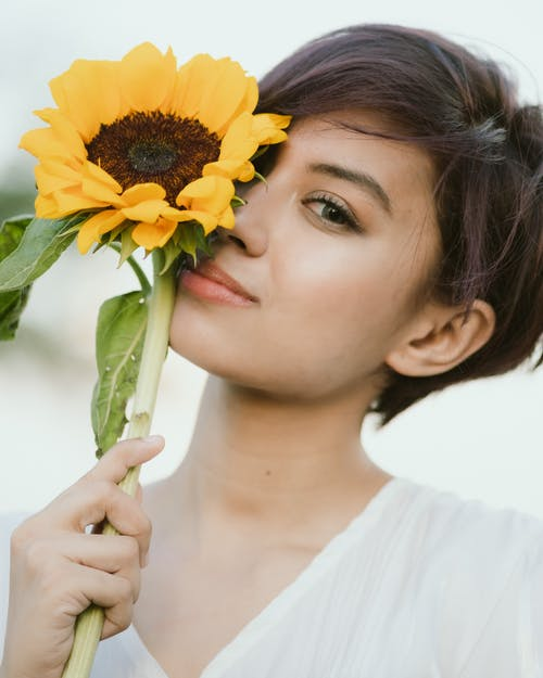 Charming woman with short brown hair and light makeup holding fresh sunflower and looking at camera