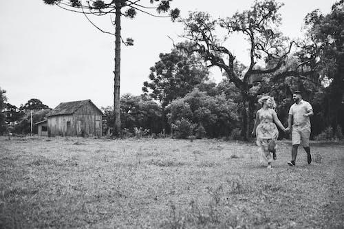 A Couple Running on a Grassland