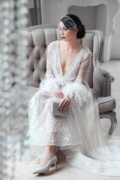 Full length calm graceful bride wearing luxurious white gown sitting on comfy armchair in studio