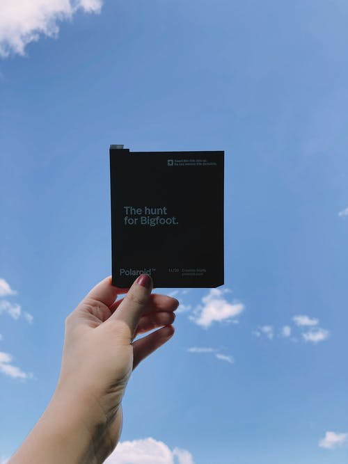Perspective view of unrecognizable person holding black case for instant pictures under clear blue sky