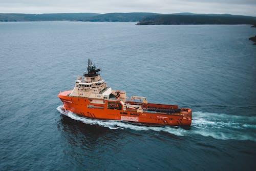 Orange and White Boat Sailing on Sea