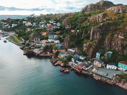 Drone view of picturesque pier with bright buildings rounded with blue endless sea