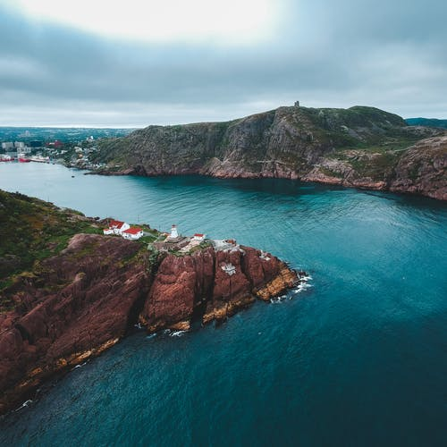 Rocky cliff of stony coast among turquoise water