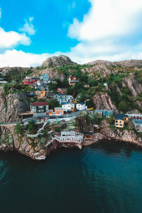 Drone view of picturesque rocky coast covered with bright small buildings near pier washed by calm ocean under blue cloudy sky