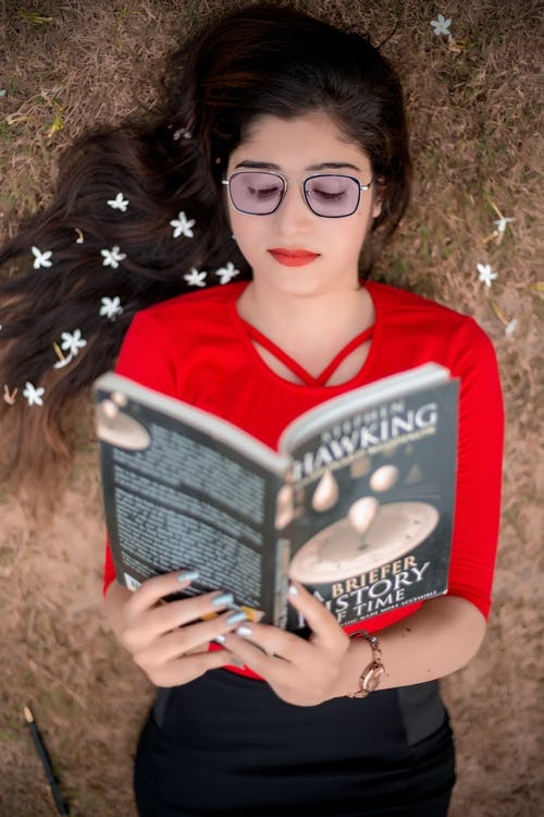 Photo of Woman in Red Top Reading a Book