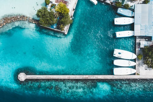 Aerial top view motorboats moored on turquoise seawater near long pier and coastal settlement on sunny day