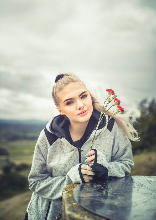 Photo of Woman in Gray Hoodie While Holding Red Flowers