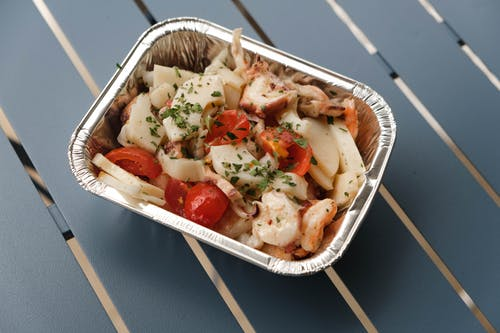 From above of tasty squids with tomatoes and herbs under sauce in foil container on blue metal table