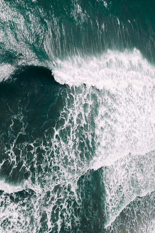 Drone view of white foamy waves of powerful ocean rolling near coast on sunny day