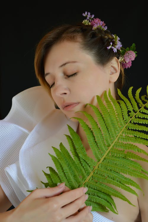 Photo of Woman in White Top Holding Fern Plant
