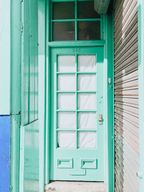 Exterior of old green wooden door with small curtained windows at sunny day
