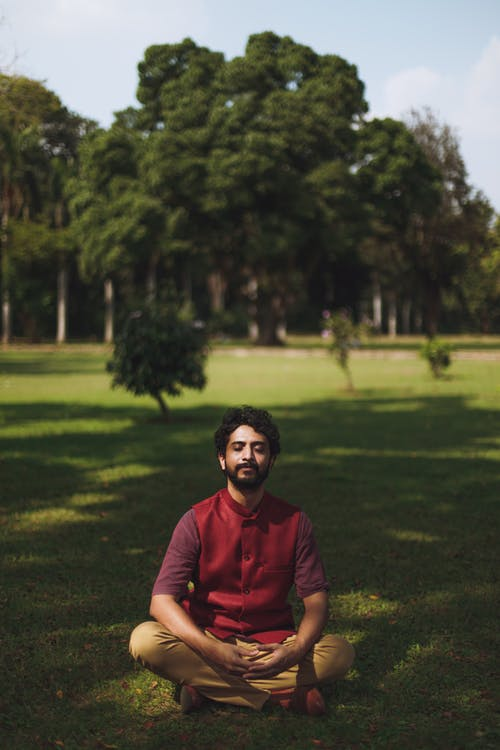 Man in Red Polo Shirt Sitting on Green Grass Field