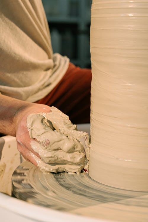Close-Up Shot of a Person Molding a Pot