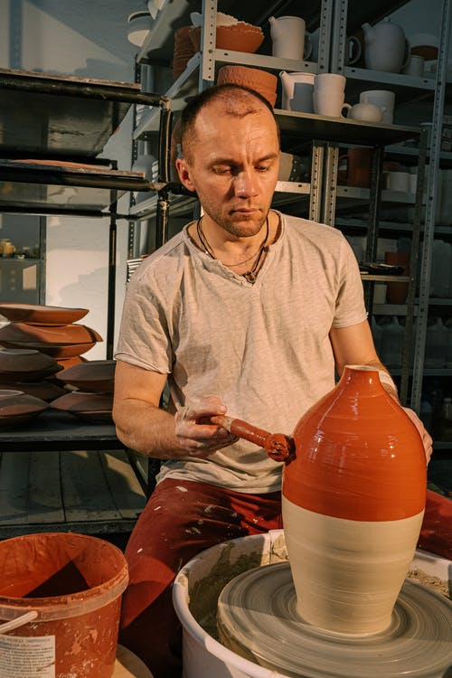Photo of Man Painting Clay Jar With Color Brown